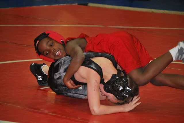 Mission Arlington student (in red) wrestling at our first tournament in early January