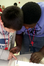 Two students participate in a Bible drill, looking up particular scriptures as fast as they can