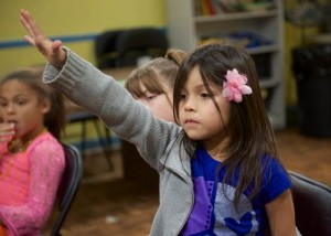 A young girl asks her Bible study teacher a question at an after-school program in central Arlington