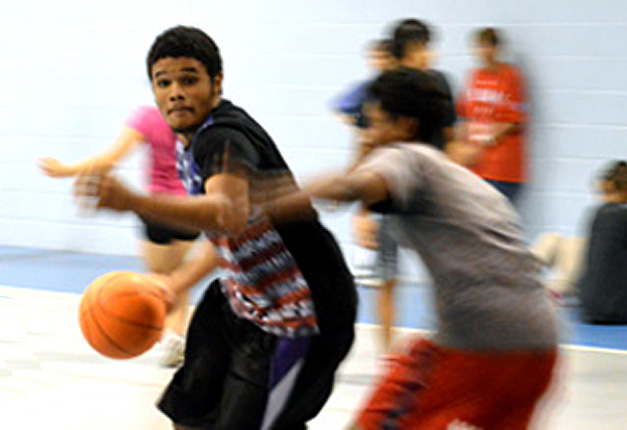 Driving to the basket at a Mission Arlington youth gym night.