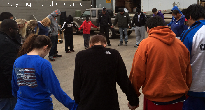 Joining hands to pray - next to the carport - at Mission Arlington